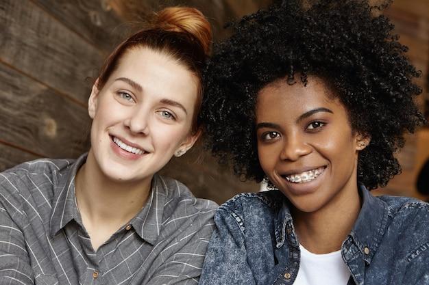 Innenaufnahme von zwei glücklichen schönen lesben verschiedener ethnien, die spaß haben
