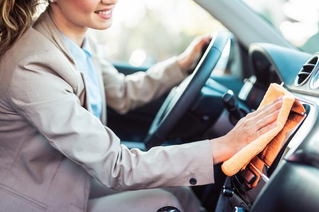 Innenausstattung des autos. glückliche geschäftsfrau wischt und reinigt den innenraum ihres autos.