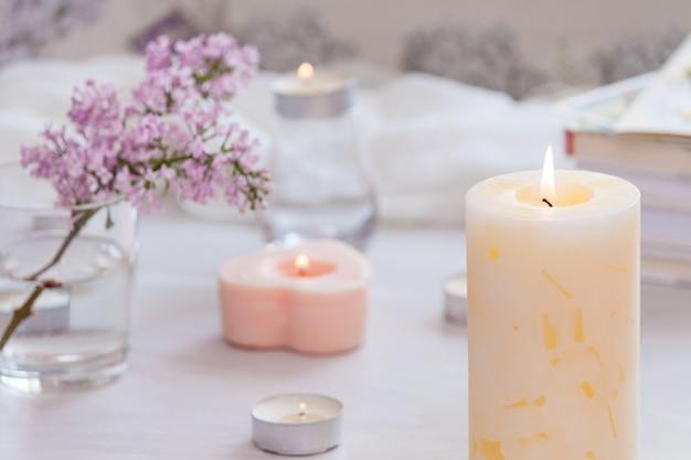 Innenausstattung des pastellzimmers mit brennender handgemachter kerze, büchern, blumen. gemütliches und entspannendes konzept.