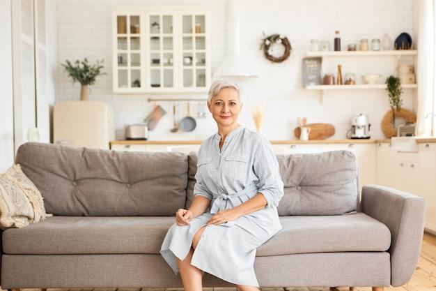 Innenbild der attraktiven eleganten kaukasischen pensionierten frau mit kurzer grauer frisur, die stilvolles blaues kleid trägt, das auf sofa in entspannter haltung sitzt und mit ruhigem freudigem lächeln schaut. menschen und alter