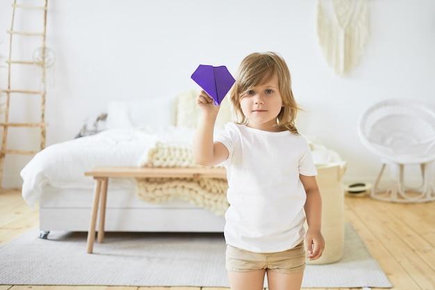 Innenbild des charmanten kleinen europäischen mädchens in der freizeitkleidung spielt drinnen und hält mit violettem papierflugzeug. kinder, spaß, spiel, aktivität und freizeit