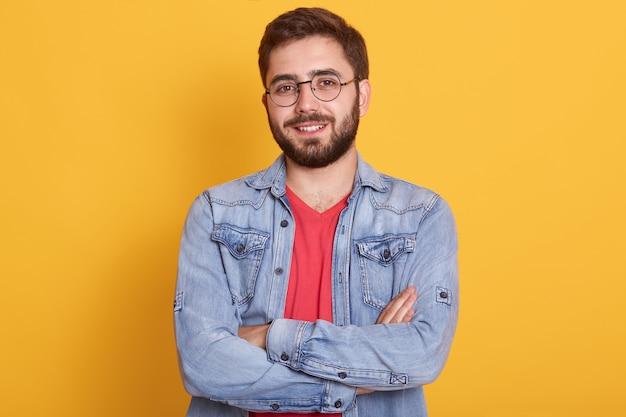 Innenbild des fröhlichen gutaussehenden jungen mannes, der hände gefaltet hat, direkt aufrichtig lächelnd schaut und freizeitkleidung trägt