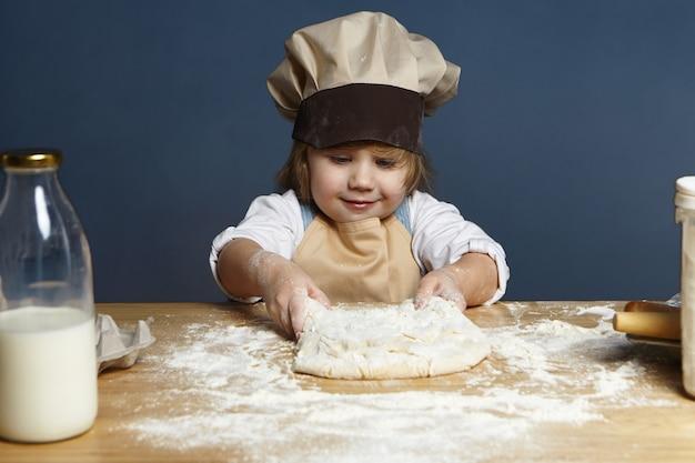 Innenbild des schönen fröhlichen europäischen kleinen mädchens in der kopfbedeckung des küchenchefs und in der schürze, die teig am küchentisch kneten und brot oder kuchen machen. konzept für gebäck, kochen, backen, backen und zubereiten