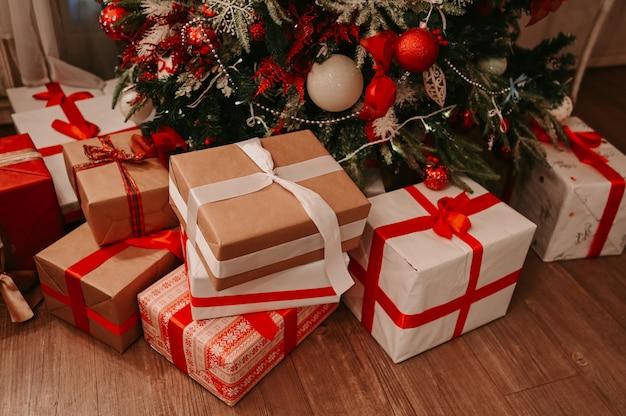 Innendetails des klassischen raumes neuen jahres mit verziertem weihnachtsbaum und geschenkboxen auf dem boden