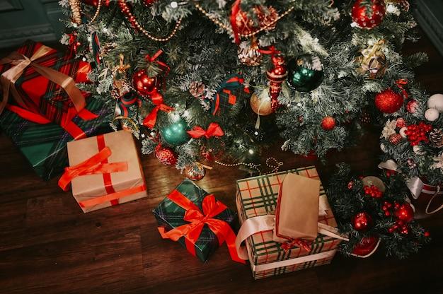Innendetails des klassischen raumes neuen jahres mit verziertem weihnachtsbaum und grün mit geschenkboxen auf dem boden
