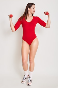 Innenfoto der arme, der taille und des bauches der jungen fitnessfrau, die trainieren, mit hanteln arbeiten, die über weißer wand lokalisiert werden, weibliches beobachten auf ihren händen, mädchen, das kombikleid trägt.