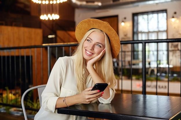 Innenfoto der bezaubernden jungen blonden frau im weißen hemd und im braunen hut, der über caféinnenraum sitzt, kopf auf ihrer handfläche lehnt und verträumt beiseite schaut