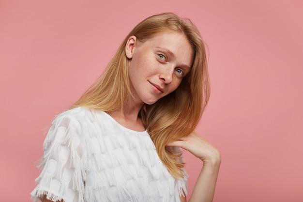 Innenfoto der bezaubernden jungen rothaarigen frau mit natürlichem make-up gekleidet in eleganter kleidung, die positiv in die kamera schaut und sanft lächelt, lokalisiert über rosa hintergrund