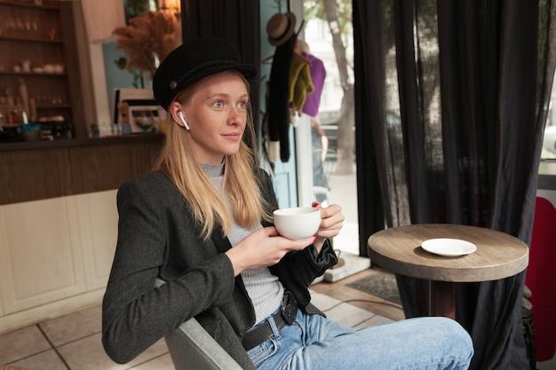 Innenfoto der jungen attraktiven blonden dame in eleganten kleidern, die am tisch über dem innenraum des cafés sitzen, tasse kaffee in erhobenen händen halten und mit konzentriertem gesicht nach vorne schauen