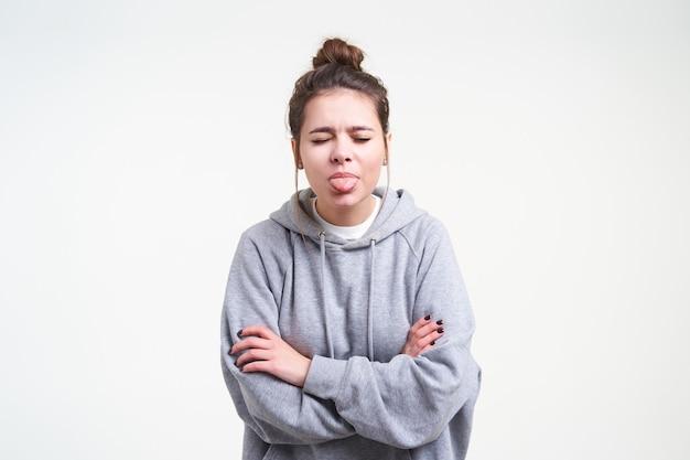 Innenfoto der jungen braunhaarigen frau mit lässiger frisur, die zunge mit geschlossenen augen und faltenden händen auf ihrer brust zeigt, während sie über weißem hintergrund aufwirft