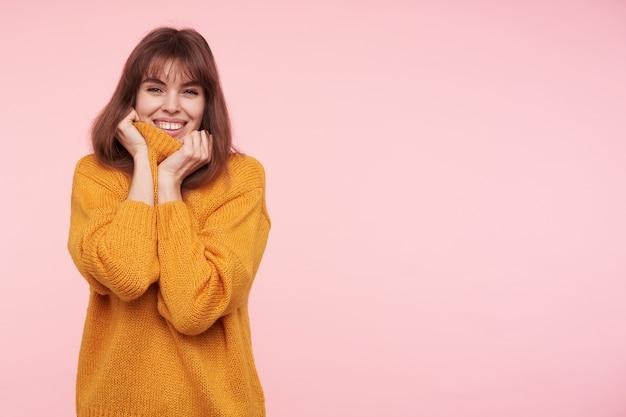 Innenfoto der jungen fröhlichen dunkelhaarigen frau mit lässiger frisur, die glücklich mit charmantem lächeln schaut, während sie über rosa wand im kuscheligen senfpullover posiert