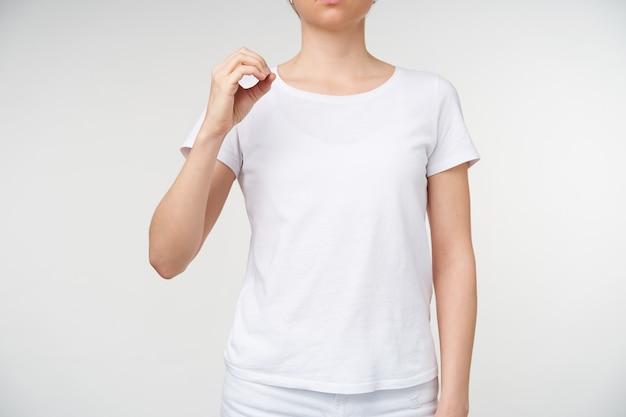Innenfoto der jungen hellhäutigen frau, die kreis mit ihrem finger bildet, während sie todesalphabet lernt und buchstaben o zeigt, während sie über weißem hintergrund aufwirft