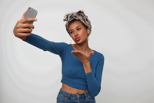 Innenfoto der jungen hübschen dunkelhaarigen lockigen frau mit gesammeltem lockigem haar, das ihre hand erhöht hält, während selfie auf smartphone und falten der lippen im luftkuss, lokalisiert über weißem hintergrund
