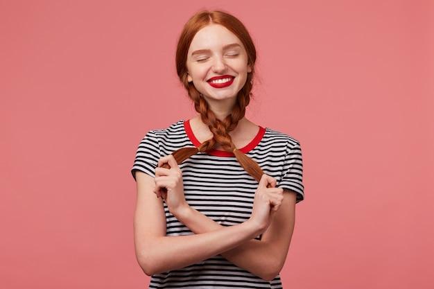 Innenfoto des hübschen rothaarigen mädchens mit den roten lippen, die mit zwei zöpfen in den händen spielen, gekleidet in abgestreiftem t-shirt, träume stellt glückliche momente mit geschlossenen augen isoliert vor