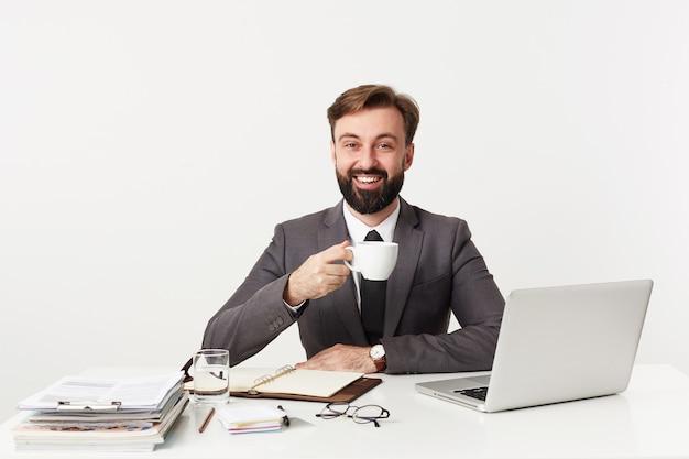 Innenfoto des positiven jungen bärtigen brünetten mannes, der guten arbeitstag hat und glücklich nach vorne lächelt, während er am tisch über weißer wand sitzt und tasse kaffee während der pause hält