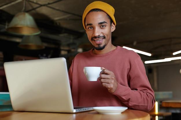 Innenfoto des schönen jungen bärtigen mannes mit der dunklen haut, die im modernen büro arbeitet, am tisch über kaffeepunkt mit tasse in der erhabenen hand sitzt und freizeitkleidung trägt