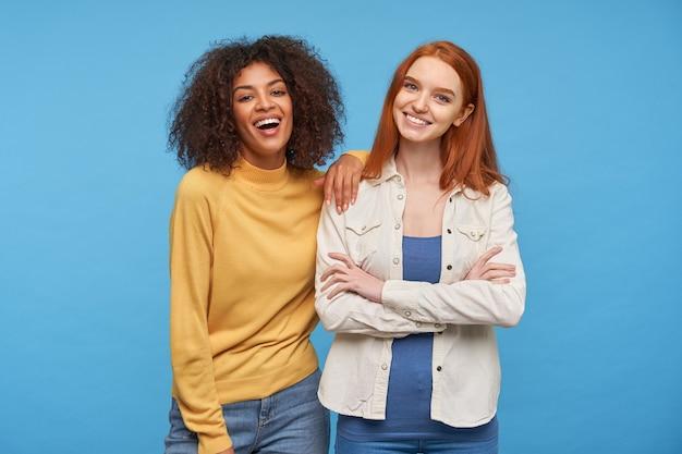 Innenfoto von charmanten fröhlichen jungen damen, die ihre angenehmen gefühle zeigen, während sie über blauer wand stehen und breit lächeln, gekleidet in lässige bequeme kleidung