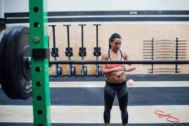 Innengymnastik der jungen sportiven sportlerin unter verwendung smartwatch