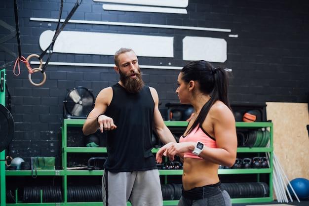 Innengymnastik des jungen persönlichen trainers, die mit sportlerin spricht