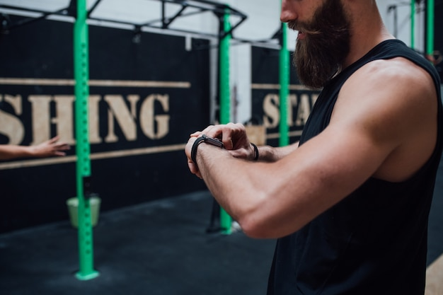 Innengymnastik des jungen sportiven manntrainers unter verwendung smartwatch