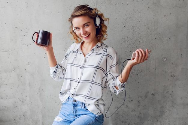 Innenlebensstilporträt der fröhlichen erfolgreichen frau, die musik hört und tasse tee hält. sie sitzt auf einem stuhl auf grauem stadtwandhintergrund.