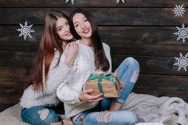 Innenlebensstilporträt von zwei hübschen jungen lustigen freundinnen umarmt lächelnd