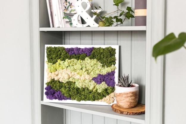 Innenlichtwand mit einem bild von moos, weißen wänden, pflanzen, kerzen und rahmen