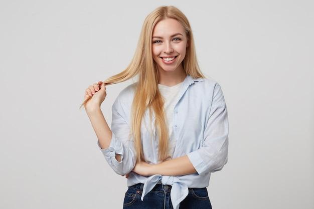 Innenporträt der angenehm aussehenden jungen blonden frau, die lächelt, eine haarsträhne hält und freizeitkleidung trägt