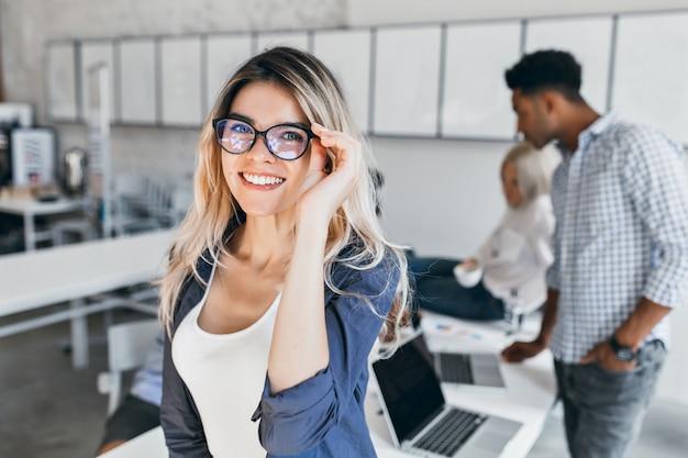 Innenporträt der aufgeregten studentin in brille und grauer jacke. attraktive mitarbeiterin, die im büro posiert und mit kollegen lacht.