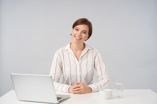 Innenporträt der bezaubernden positiven jungen braunhaarigen dame mit natürlichem make-up, das ihre hände auf tisch faltet und fröhlich mit angenehmem lächeln schaut, das auf weiß aufwirft