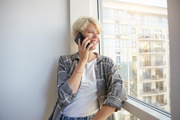 Innenporträt der blonden hübschen frau in der freizeitkleidung, die am telefon spricht, sich auf fenster lehnt und auf die straße schaut, in der guten stimmung ist