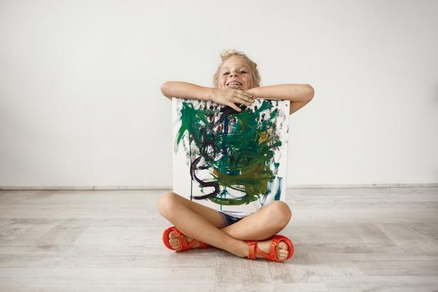 Innenporträt der blondine, die mit ihren zähnen lächelt, kleines mädchen, das mit gekreuzten beinen auf dem boden sitzt und das bild umarmt, das sie für ihre eltern gemalt hat. glückliches weibliches kind, das stolz auf sich selbst ist. menschen und pos