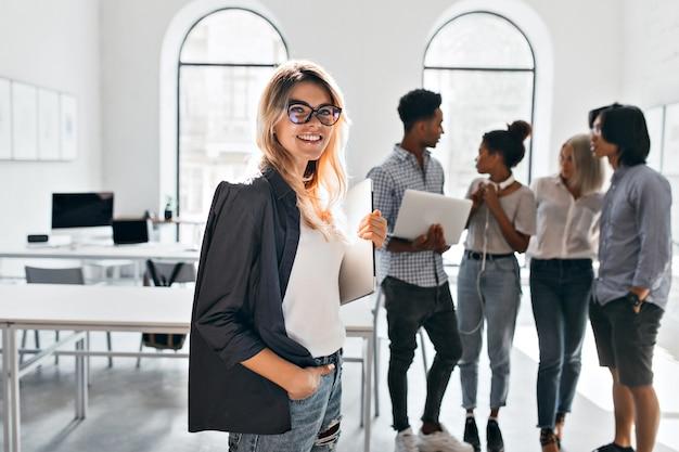 Innenporträt der eleganten geschäftsdame in der schwarzen jacke und ihrem team. afrikanischer büroleiter in weißen turnschuhen, die laptop tragen und mit mulattin in jeans sprechen.