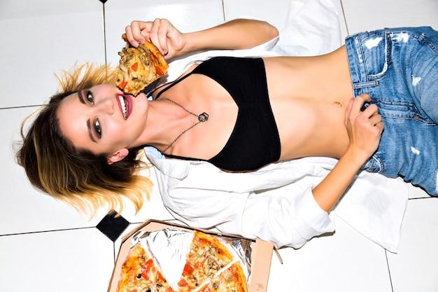 Innenporträt der fröhlichen glücklichen jungen frau mit dem stück der köstlichen heißen pizza, die auf boden legt. schwarze unterwäsche, weißes hemd, stylische jeans. perfekter schlanker körper. diätkonzept