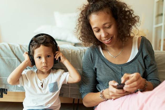 Innenporträt der fröhlichen jungen hispanischen frau, die handy hält, das musiktitel für ihren entzückenden kleinen sohn spielt, der lieder über drahtlose kopfhörer hört