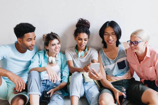 Innenporträt der fröhlichen studenten, die ihre telefone halten und lächeln. anmutige afrikanische mädchen in kopfhörern und jeans machen selfie mit freunden in der universität ..