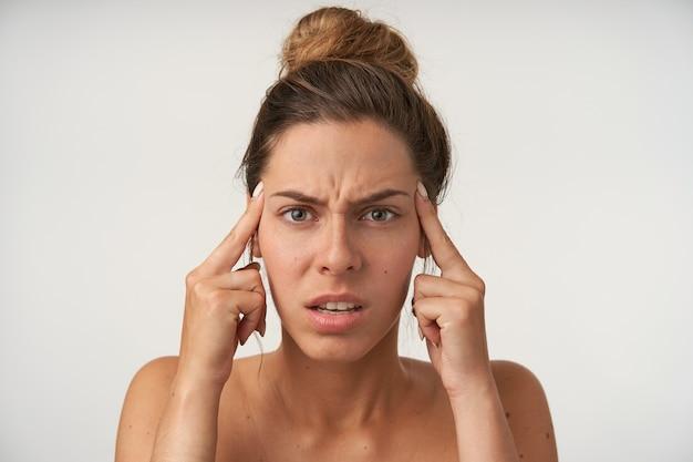 Innenporträt der gestressten jungen hübschen frau, die auf weiß mit hoher brötchenfrisur aufwirft, die stirn runzelt und zeigefinger an den schläfen hält