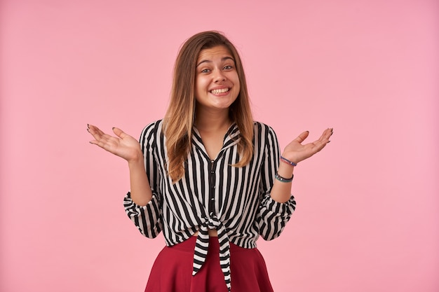 Innenporträt der glücklichen jungen braunhaarigen dame mit natürlichem make-up, das mit erhobenen händen zuckt und breit lächelt, während sie gegen rosa steht