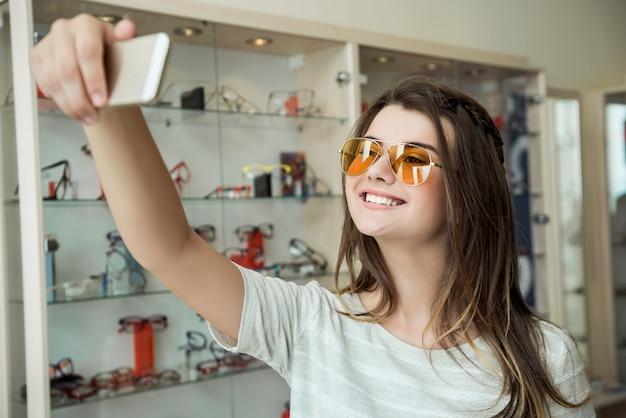 Innenporträt der gutaussehenden jungen frau im optikergeschäft, das eine neue sonnenbrille kauft, um die augen vor der sonne zu schützen