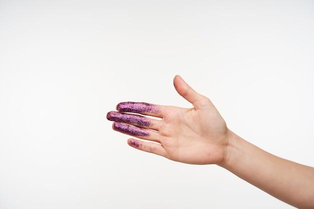 Innenporträt der hand der erhabenen jungen frau, die handfläche zeigt, während sie auf weiß posiert, mit lila schimmern darauf, jemandem die hand schüttelnd