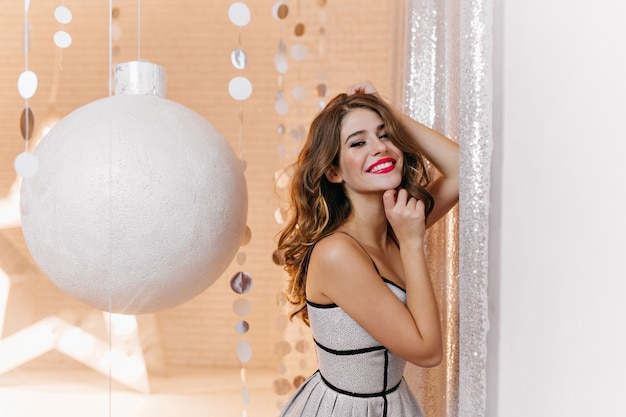Innenporträt der herrlichen frau mit festlicher neujahrsstimmung im hellen, stilvollen kleid. die lockige brünette lächelt breit