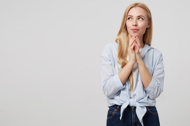 Innenporträt der hübschen blonden dame in der freizeitkleidung, die schlau beiseite schaut, handflächen zusammenhält und etwas plant, posiert