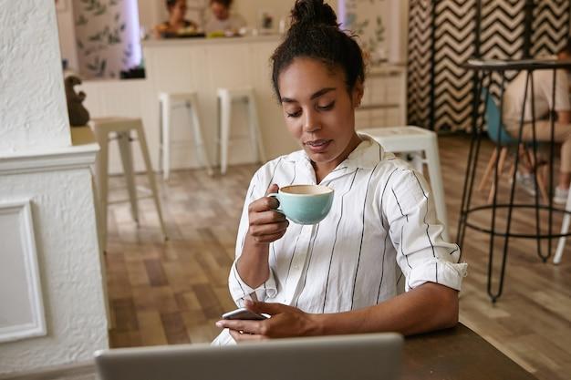Innenporträt der hübschen dunkelhäutigen frau mit brötchenfrisur, die entfernt vom café arbeitet, kaffee trinkt und bildschirm ihres smartphones betrachtet