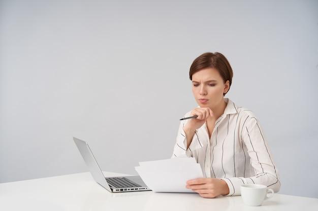 Innenporträt der jungen braunhaarigen brünetten frau mit lässiger frisur, die im modernen büro mit laptop arbeitet, dokumente mit konzentriertem gesicht prüfend, während auf weiß sitzend