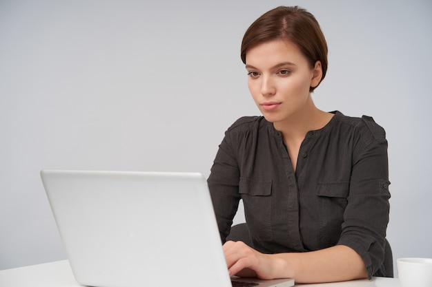Innenporträt der jungen braunhaarigen reizenden frau, die mit ihrem laptop arbeitet und bildschirm mit ruhigem gesicht betrachtet, gekleidet in formelle kleidung, während auf weiß sitzend