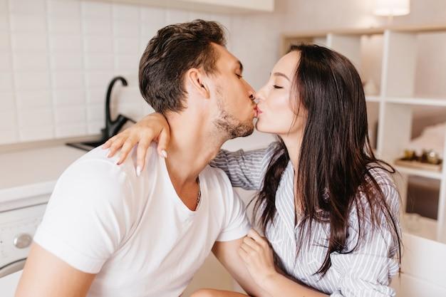 Innenporträt der jungen frau mit eleganter maniküre, die ihren dunkelhaarigen ehemann küsst