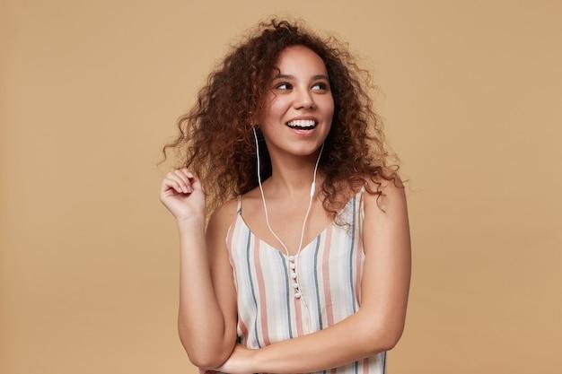 Innenporträt der jungen fröhlichen braunhaarigen lockigen dame, die fröhlich mit breitem lächeln beiseite schaut, während musik hört, lokalisiert auf beige