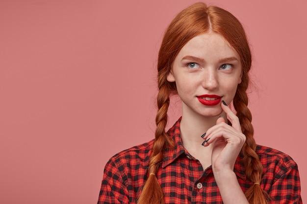 Innenporträt der jungen ingwerfrau schaut nachdenklich auf den kopierraum, während sie ihre wange mit einem finger berührt.