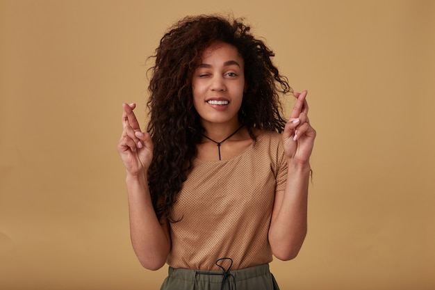 Innenporträt der jungen positiven lockigen dunkelhäutigen brünetten dame, die hände mit gekreuzten fingern erhebt und besorgniserregend unterlippt, während sie auf beige posiert