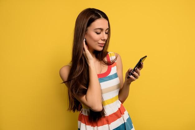 Innenporträt der liebenswerten frau mit dem langen haar, das helles kleid hält, das smartphone hält und musik in kopfhörern hört.